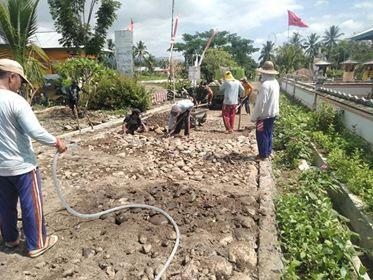 Babinsa Koramil 1303-07/Dumoga saat terjun membantu warga dalam kegiatan penataan batu untuk pengerasan jalan desa sepanjang 250 meter di Desa Mopugad Selatan.