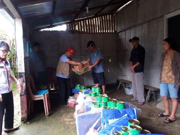 Pihak Dinsos Minahasa saat menyalurkan bantuan kepada keluarga di Desa Sendangan Tengah yang terkena musibah tanah longsor